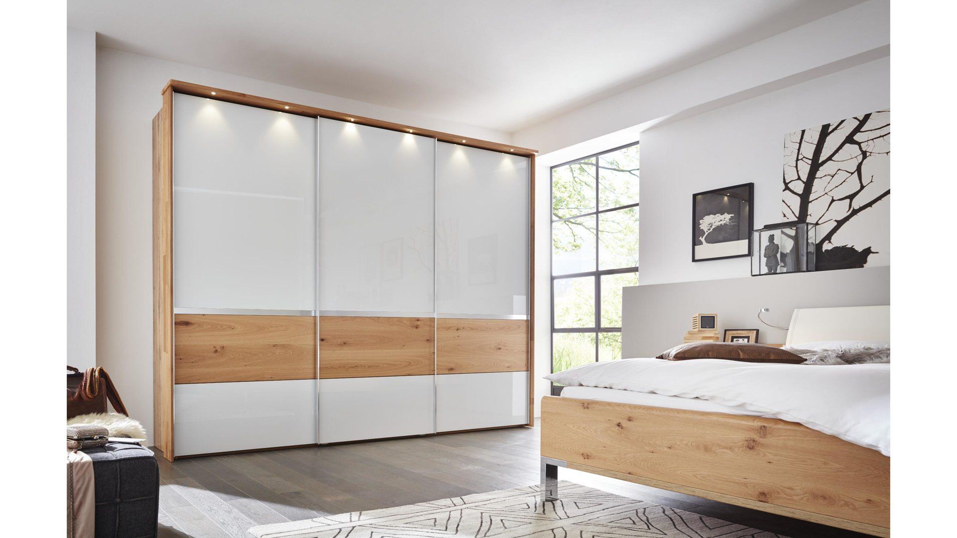 Interliving Schlafzimmer Serie 1202 – Schwebetürenschrank, teilmassive  Balkeneiche & weißes Glas – drei Türen